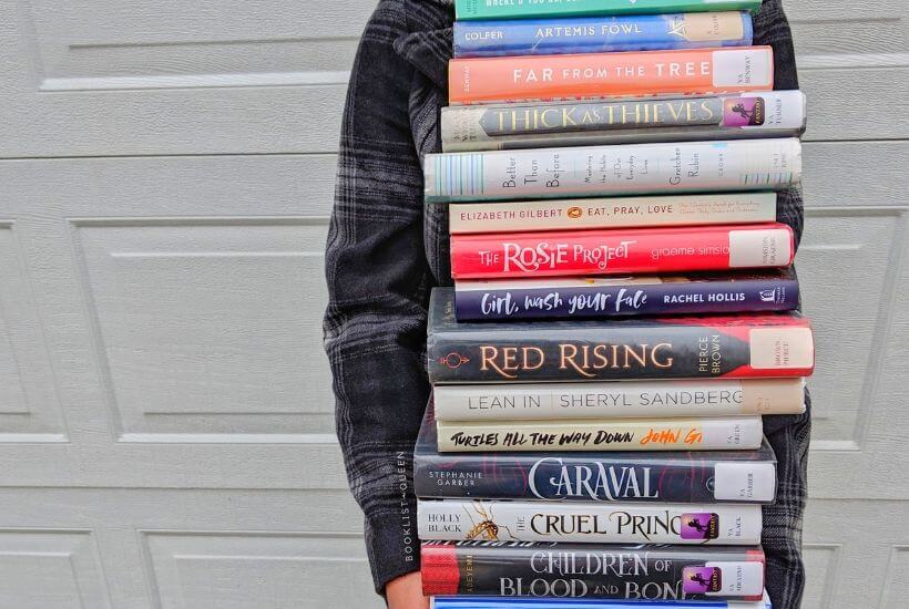 Rachael holding gigantic stack of books
