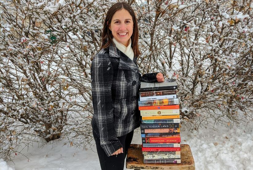 Rachael in the snow with a stack of books