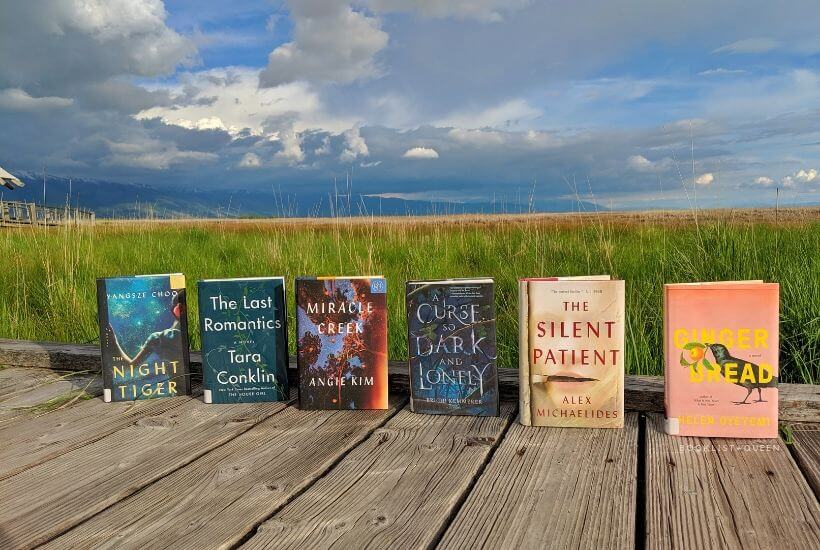 books lined up on boardwalk with wetlands in backdrop