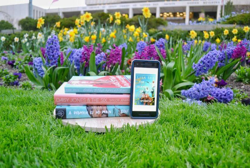 bookstack and e-book among spring flowers
