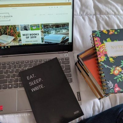 Laptop showing Booklist Queen, bookstack, notebook, 2020 planner