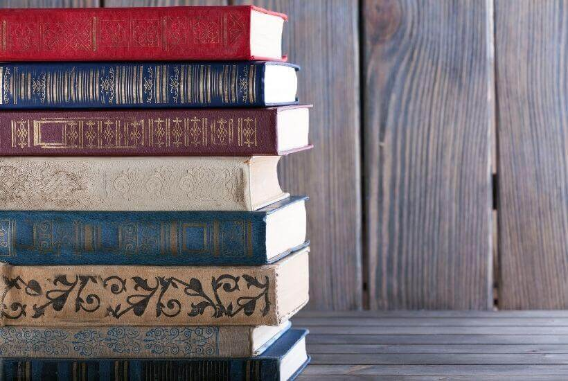 book stack, open book, teacup, purple background