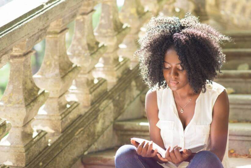 Black woman reading book on stairs
