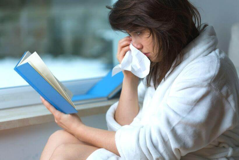 Books that make you cry - woman holding a tissue while reading a book