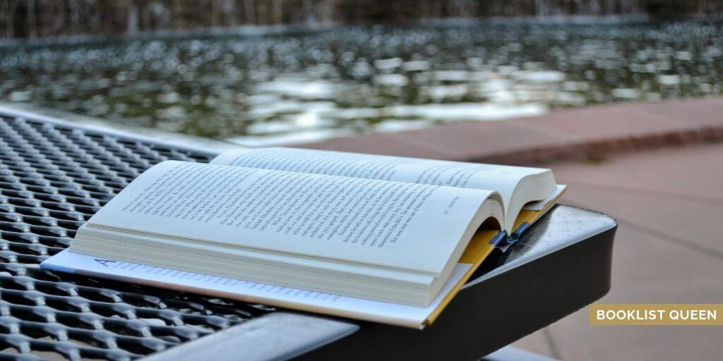 open book on picnic table by reflecting pool