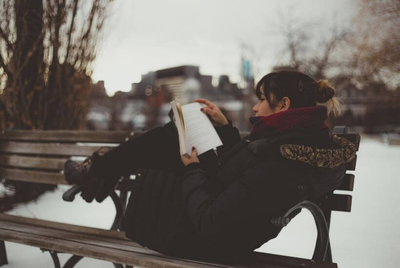 Woman reading on bench in winter