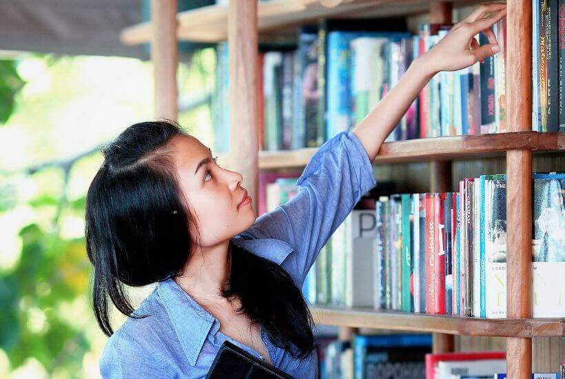 Teen Girl Choosing Book