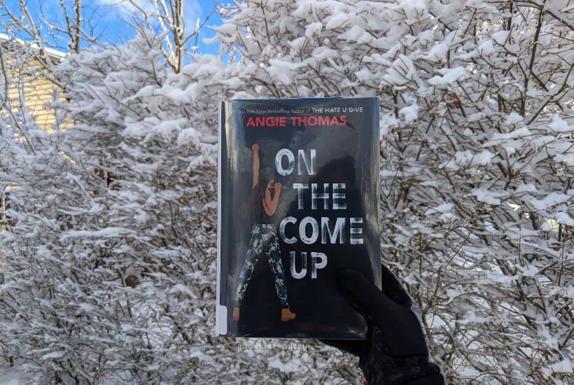 Black gloved hand holding On the Come Up by Angie Thomas against snowy backdrop
