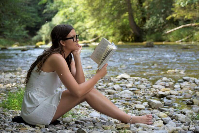 Girl reading book by stream