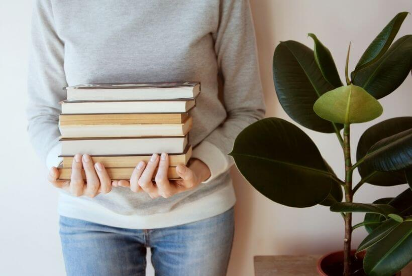 Woman holding nonfiction books next to plant