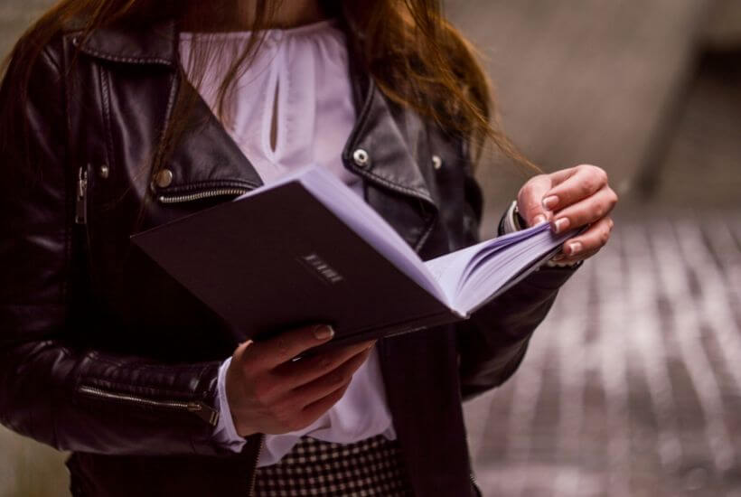 woman in leather jacket reading book