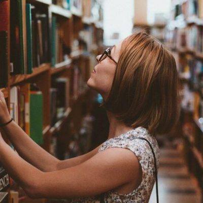 girl looking through bookshelves