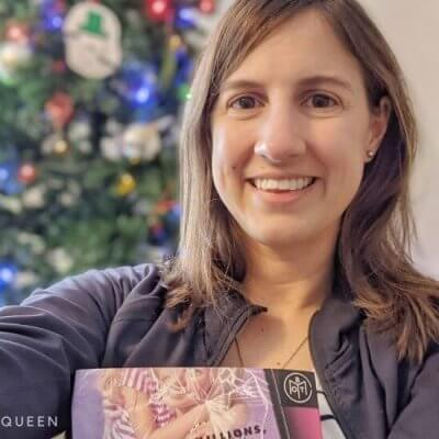 Rachael holding a book in front of the Christmas tree