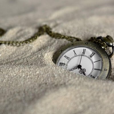 pocket watch buried in sand - Time Travel Books