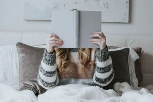woman holding book in front of face in bed